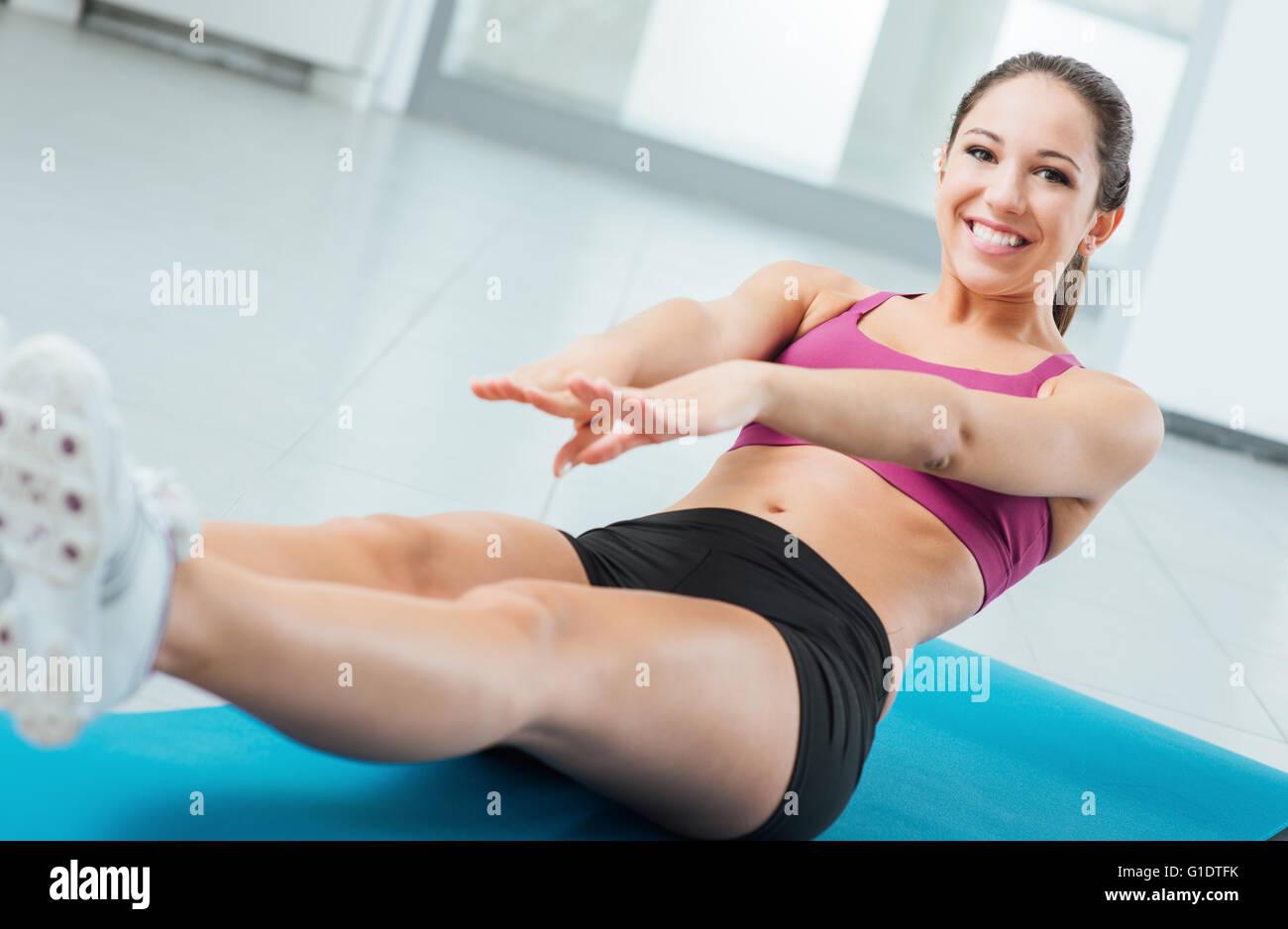 Lächelnde junge Frau Adbominal Übungen im Fitnessstudio auf einer Matte, Fitness und Workout-Konzept Stockbild