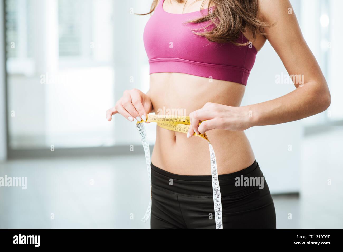 Schlanke junge Frau, die ihre dünne Taille mit einem Maßband messen, Nahaufnahme Stockbild