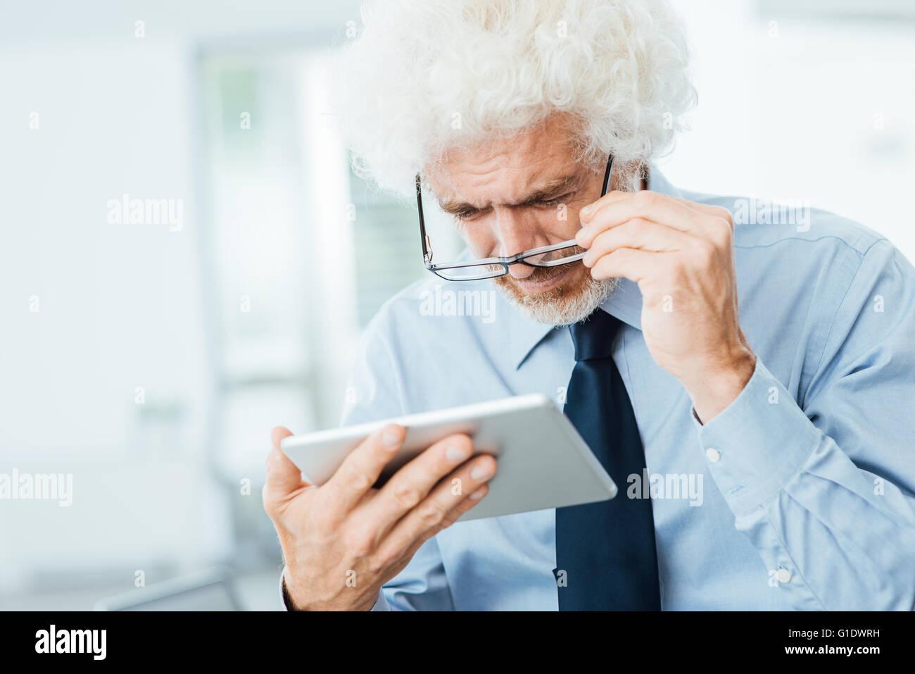 Unternehmer haben Sehprobleme, er nutzt eine Tablette und Anpassung seiner Brille, Büroeinrichtung auf Hintergrund Stockbild