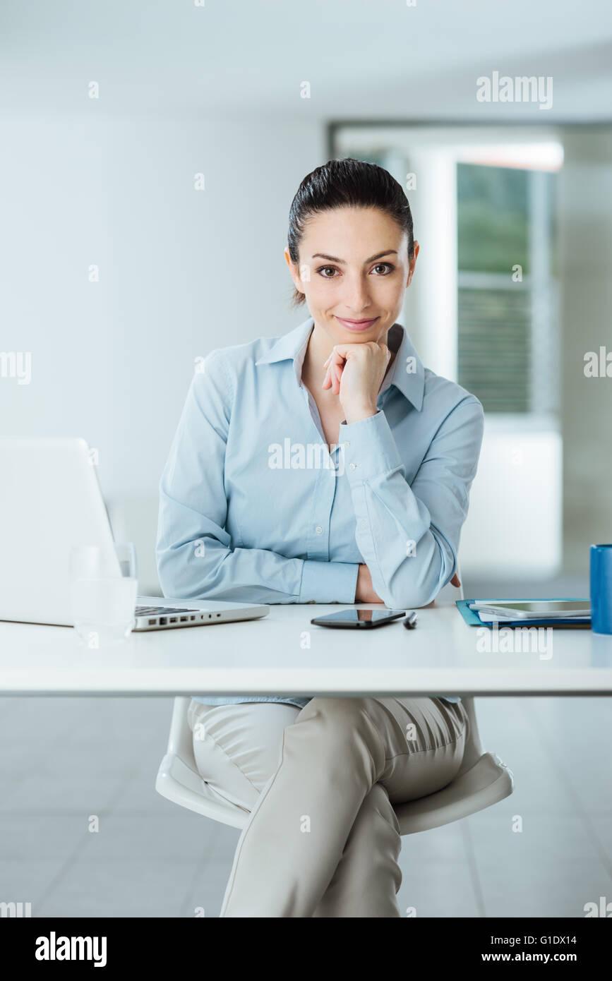 Schöne zuversichtlich Managerin am Schreibtisch sitzt und lächelt in die Kamera mit Hand am Kinn, Innenraum Stockbild