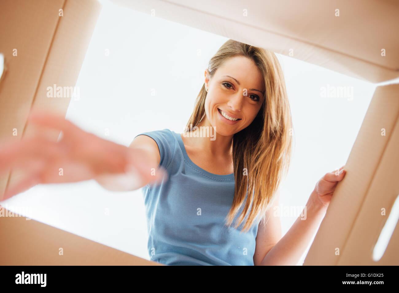 Lächelnde junge Frau einen Karton, Umzug öffnen und Auspacken Konzept Stockfoto