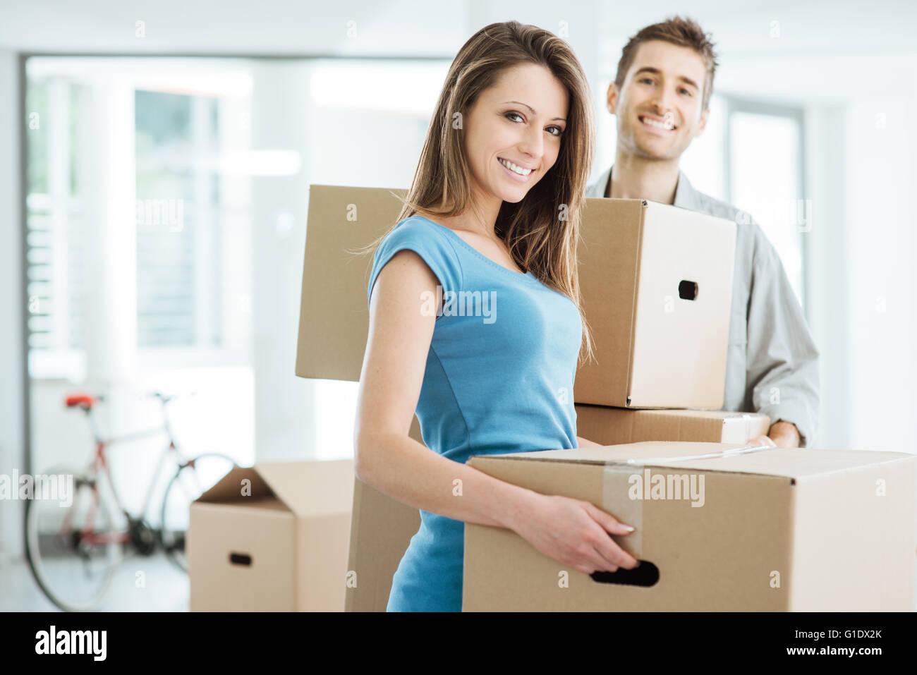 Umzug in ein neues Haus und tragen Kartons, Umzug und Renovierung Konzept lächelnden Brautpaar Stockbild