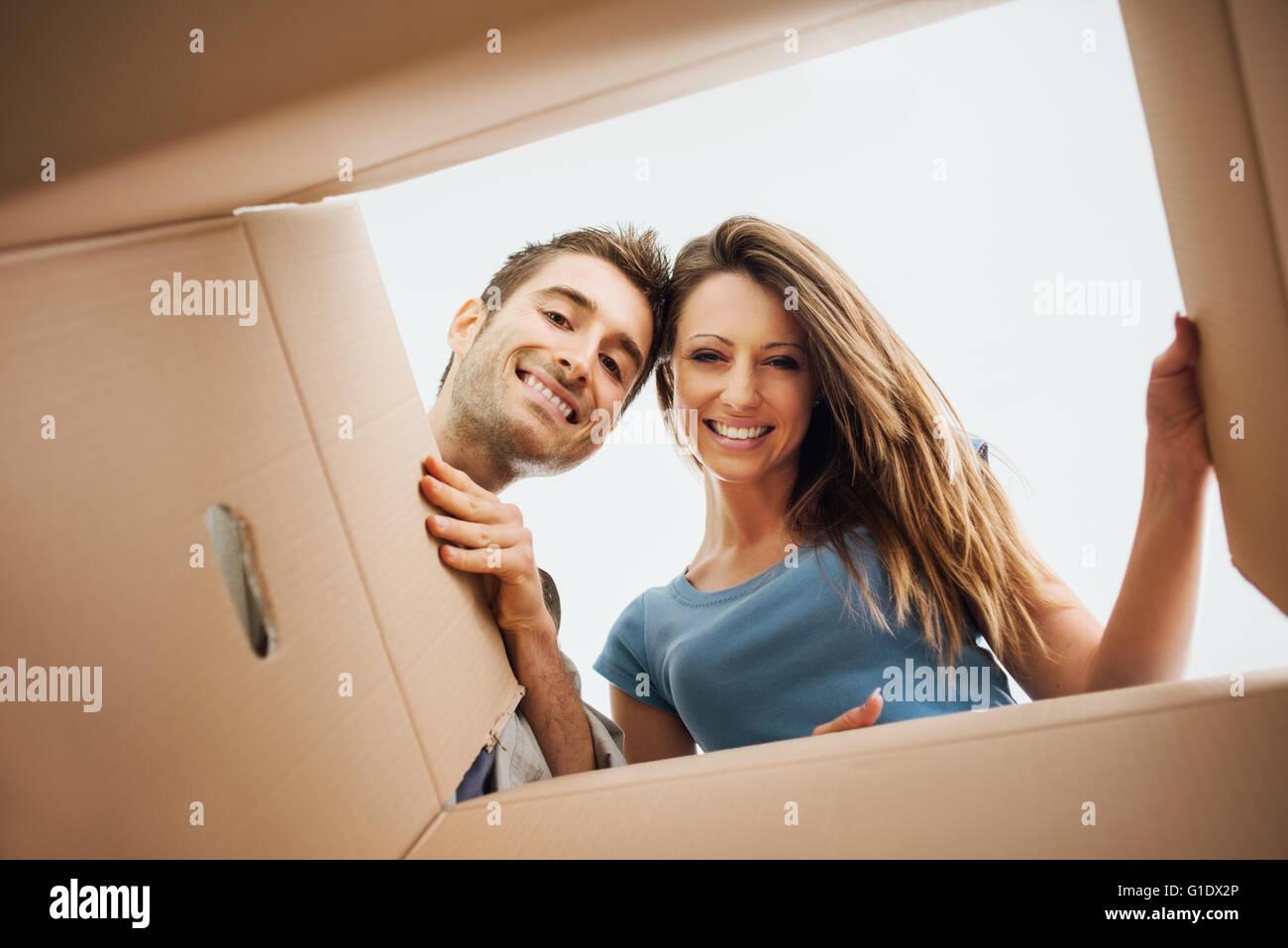 Lächelnde junge Paar einen Karton öffnen und auf der Suche nach innen, Umzug und Auspacken Konzept Stockbild