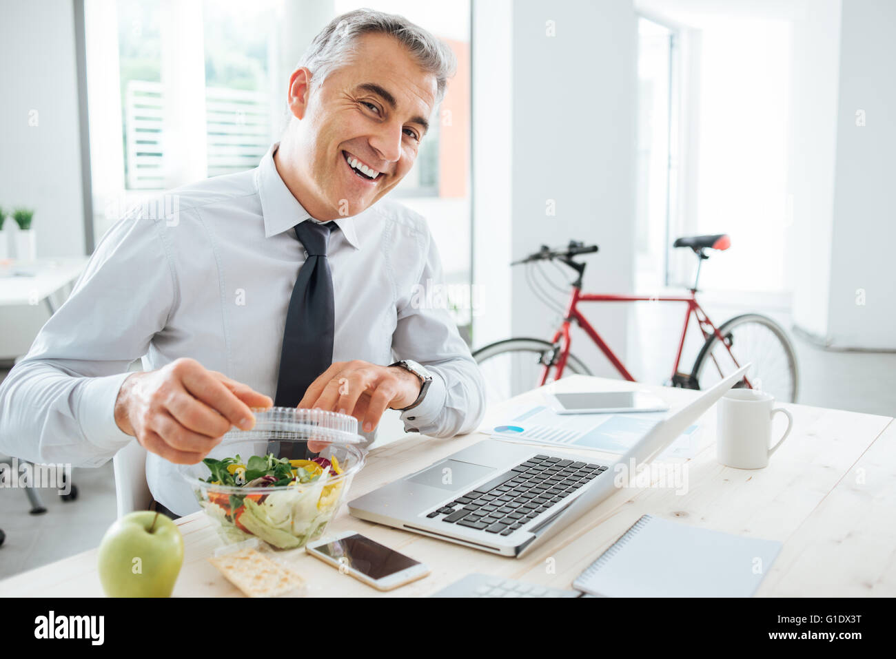 Glücklich Kaufmann brechen seinen Salat Pack öffnen und mit einem Mittagessen am Schreibtisch Stockbild
