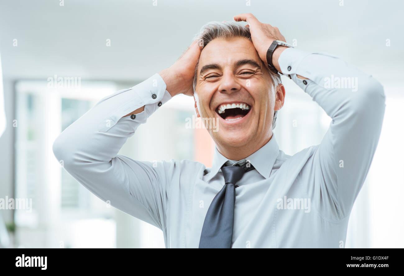 Fröhlichen sorglosen Geschäftsmann Lachen und berührte seine Stirn Stockbild