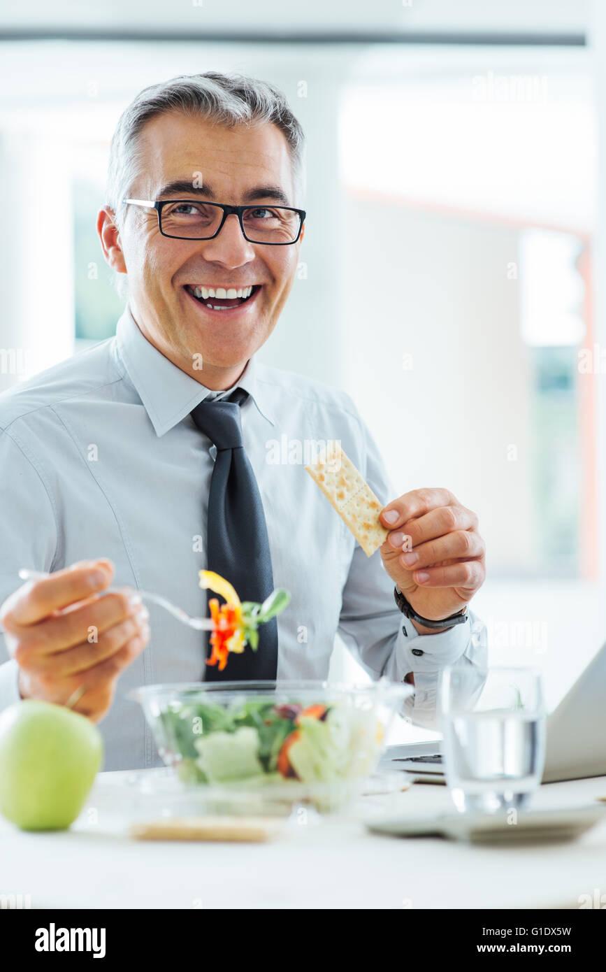Lächelnd Geschäftsmann am Schreibtisch sitzen und mit einer Mittagspause, isst er eine Salatschüssel Stockbild