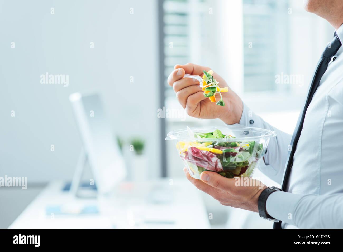 Geschäftsmann mit einem Gemüse-Salat zum Mittagessen, gesunde Ernährung und Lebensstil-Konzept, unerkennbar person Stockfoto