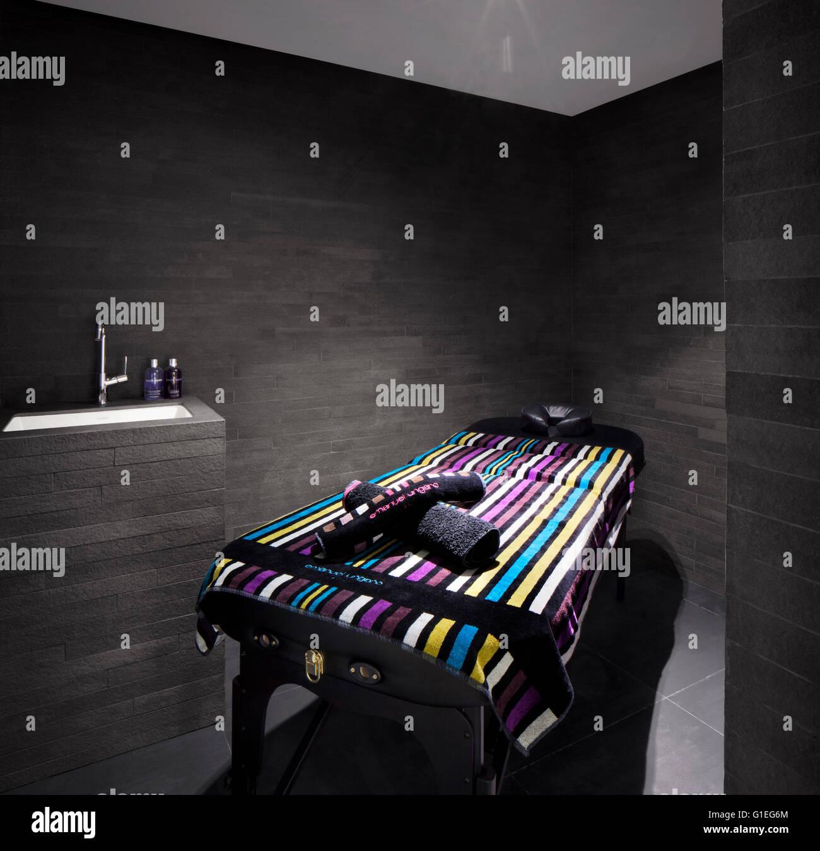Moderne Massageraum mit bunten Handtuch und einfarbige Wände und Funktionen. Stockfoto