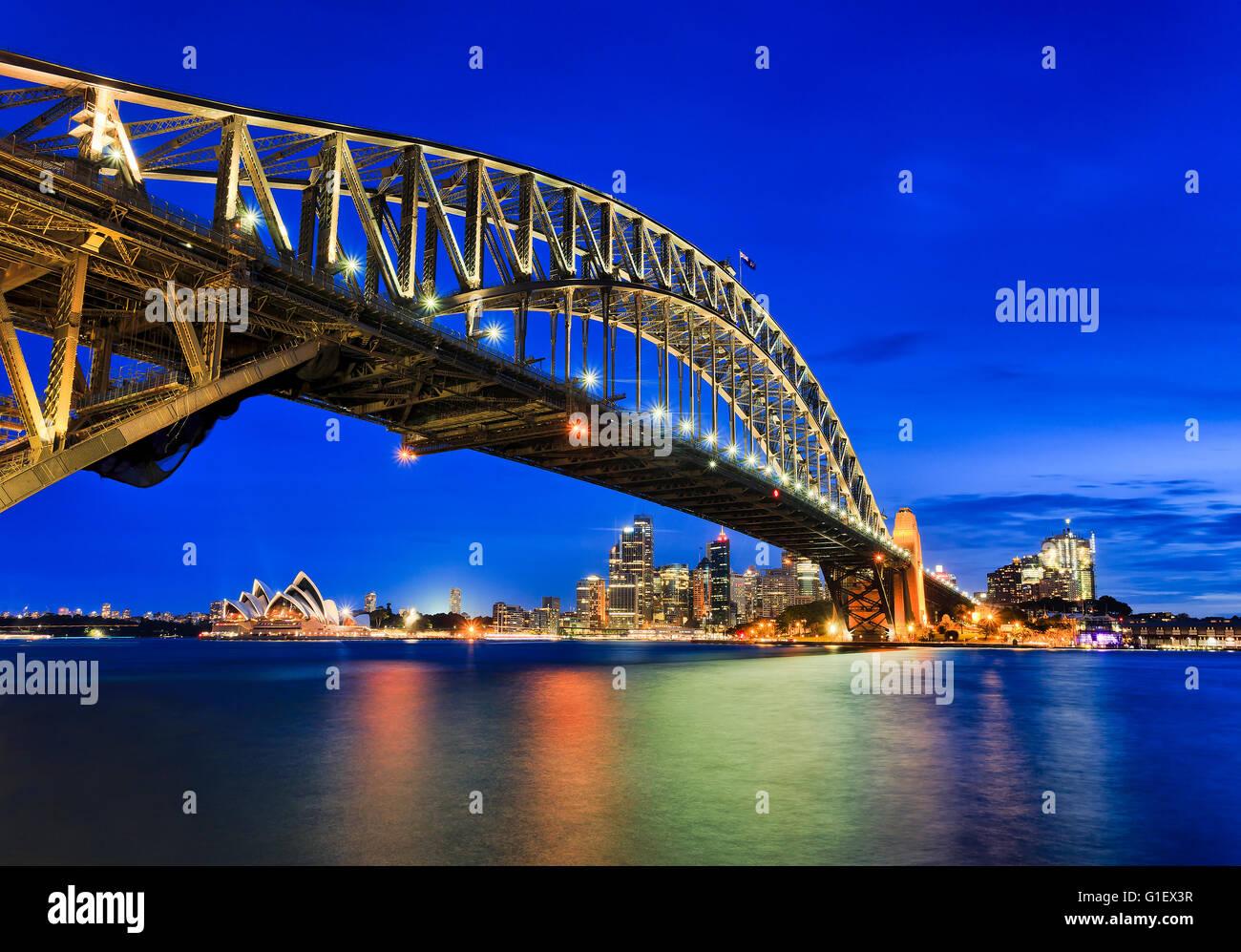 Seitenansicht der Sydney Harbour Bridge in Richtung Stadt CBD, die Felsen und Circular Quay bei Sonnenuntergang Stockfoto