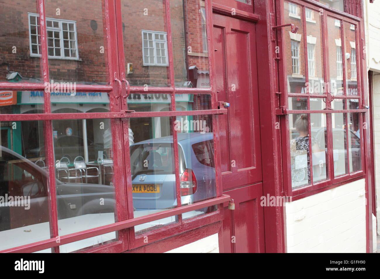 kleines rotes Quadrat-Panoramafenster mit Reflexionen Stockfoto