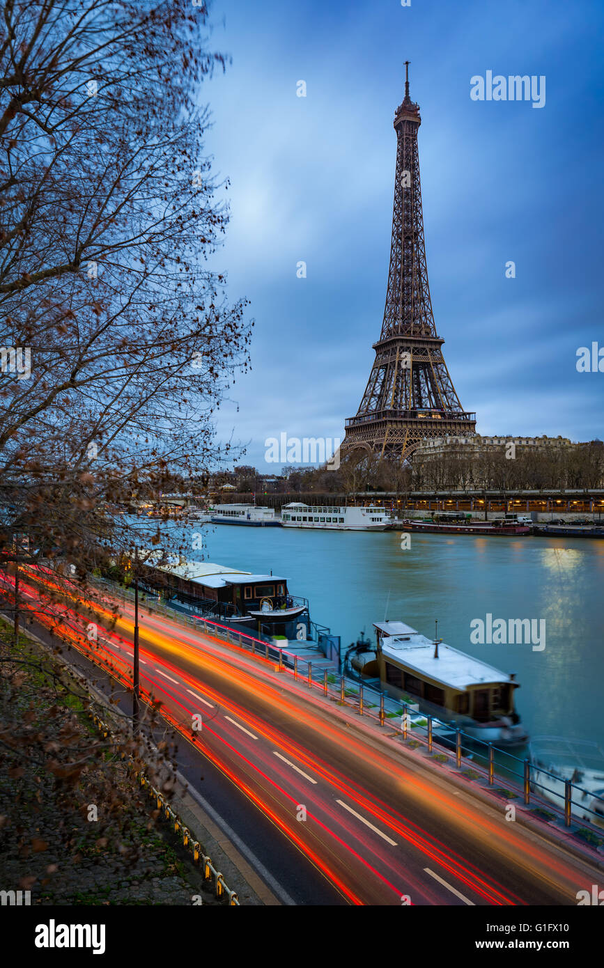 Eiffelturm in der Dämmerung an einem bewölkten Wintermorgen mit dem Seineufer und dem Auto Lichtspuren. Stockbild