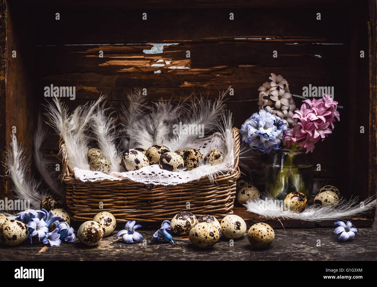 Korb mit Wachteleiern und Federn und Frühling Blumen Hyazinthen Haufen auf Vintage Holztisch über rustikale Stockbild