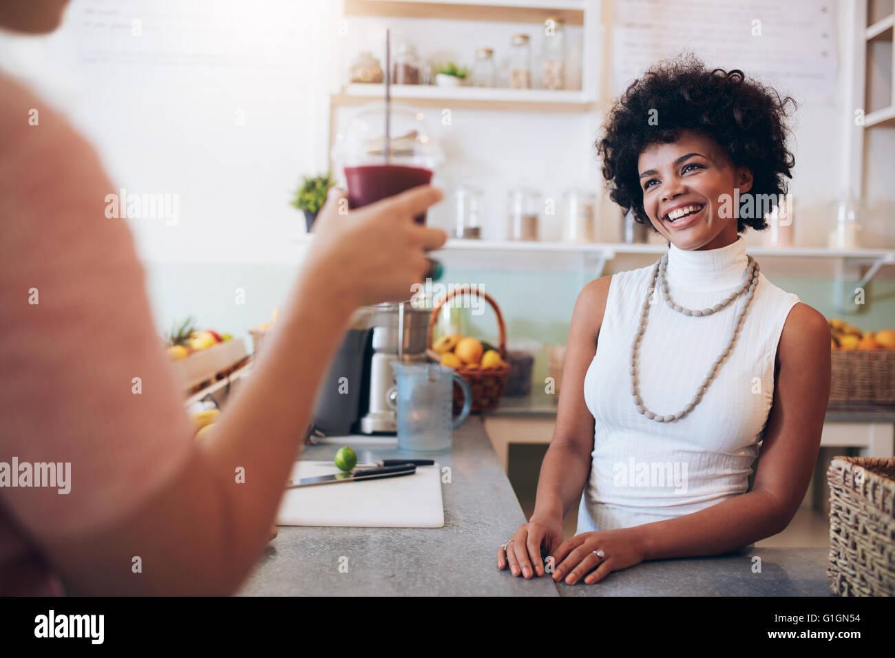 Saft-Bar-Besitzer mit weiblichen Kunden mit einem Glas frischen Saft. Afrikanische Frau hinter der Theke stehen Stockbild