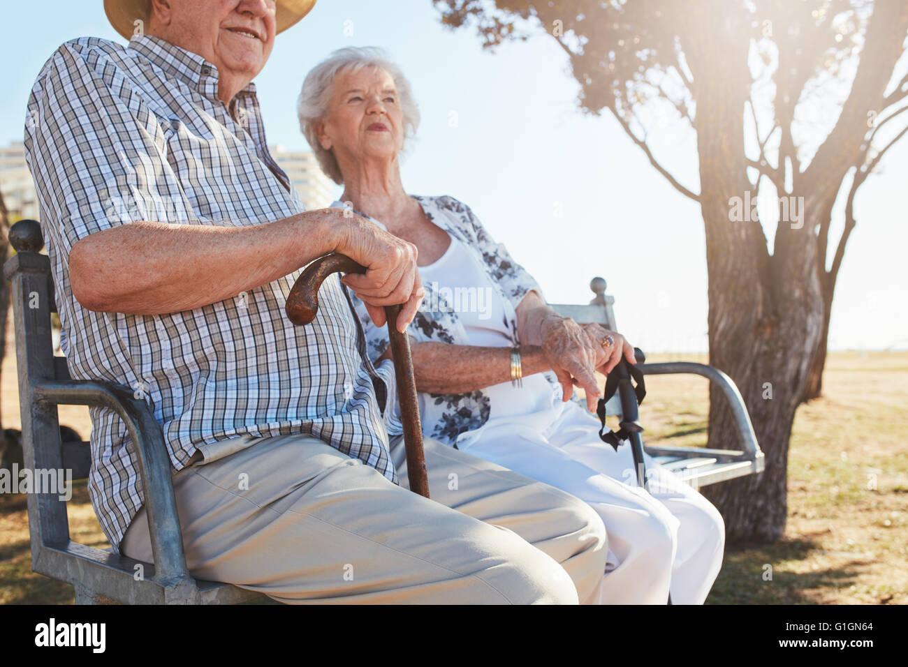 Senior paar sitzt auf einer Parkbank mit Gehstock. Älteres Paar an einem Sommertag im Freien entspannen. Stockbild