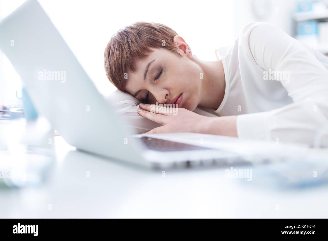 Schlafen auf ihrem Schreibtisch und stützte sich auf ihren Arm müde Geschäftsfrau Stockbild
