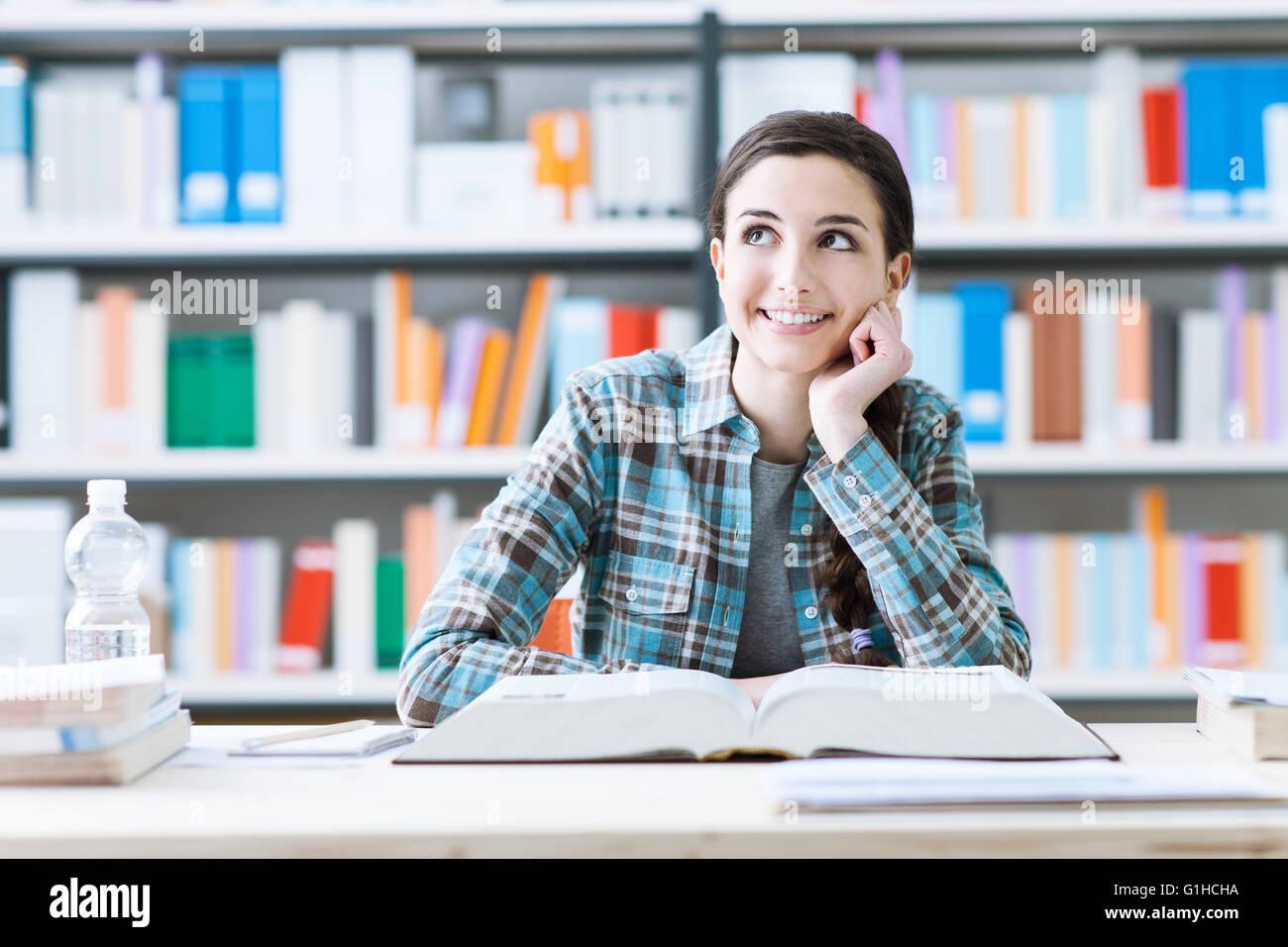 Studentin in der Bibliothek studieren und Tagträumen Lächeln, sie denkt mit Hand am Kinn und nachschlagen, Stockbild