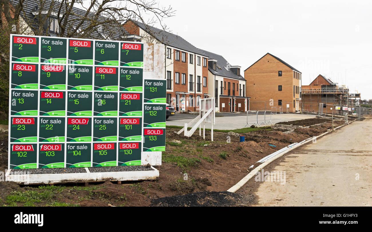 Schild mit Status des neu errichteten Häusern mit defokussierten Häuser in verschiedenen Bauphasen im Stockbild