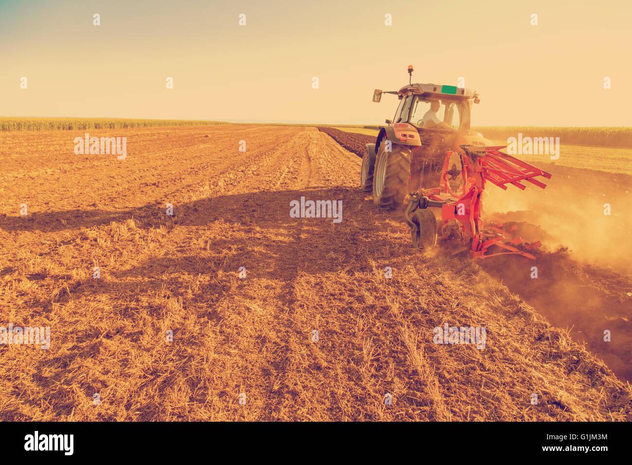 Landwirt Pflügen Stoppelfeld mit roten Traktor, Foto manipuliert, um alte Kreuz Verarbeitung Xpro Look zu erzielen. Stockbild