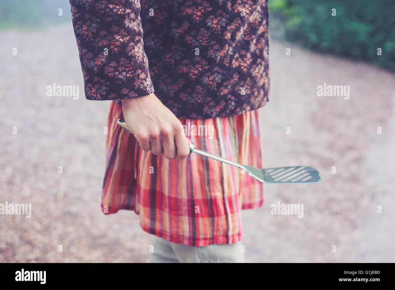 Eine junge Frau ist draußen und hält einen Spatel Stockbild