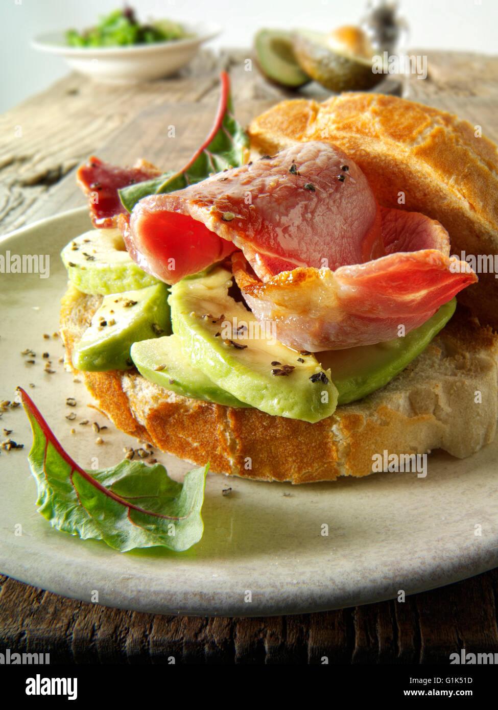 Vorbereitete Speck und Avocado Sandwich in Weißbrot auf einem Teller Stockbild
