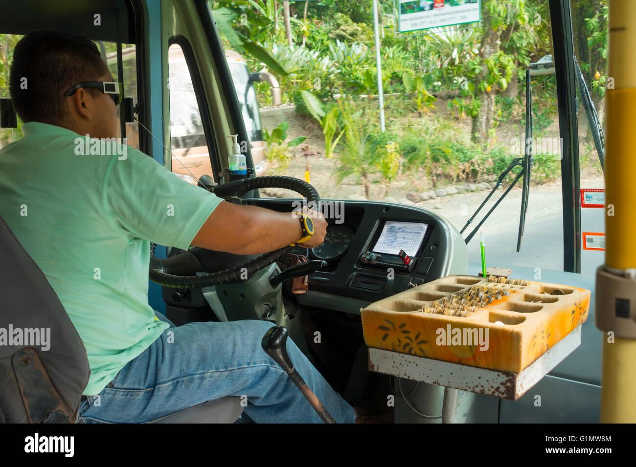 Ein Busfahrer fahren einen alten Bus mit eine altmodische Art und Weise Geld zu sammeln. Quepos, Provinz Puntarenas, Stockbild