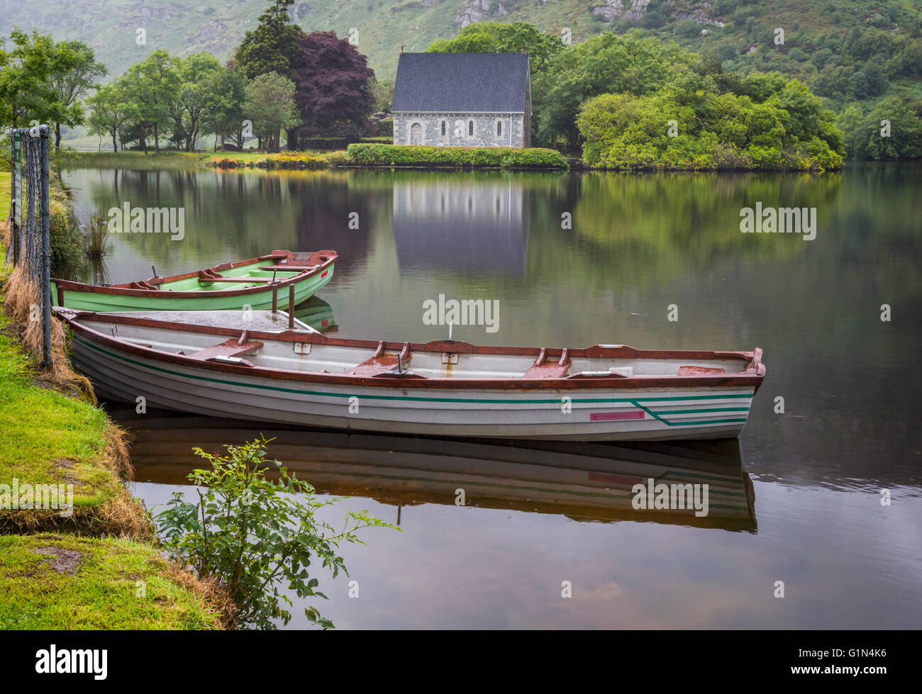 Gougane Barra, County Cork, Irland.  Eire.  Blick über Ruderboote vertäut am Ufer Sees mit der Eremitage Stockbild