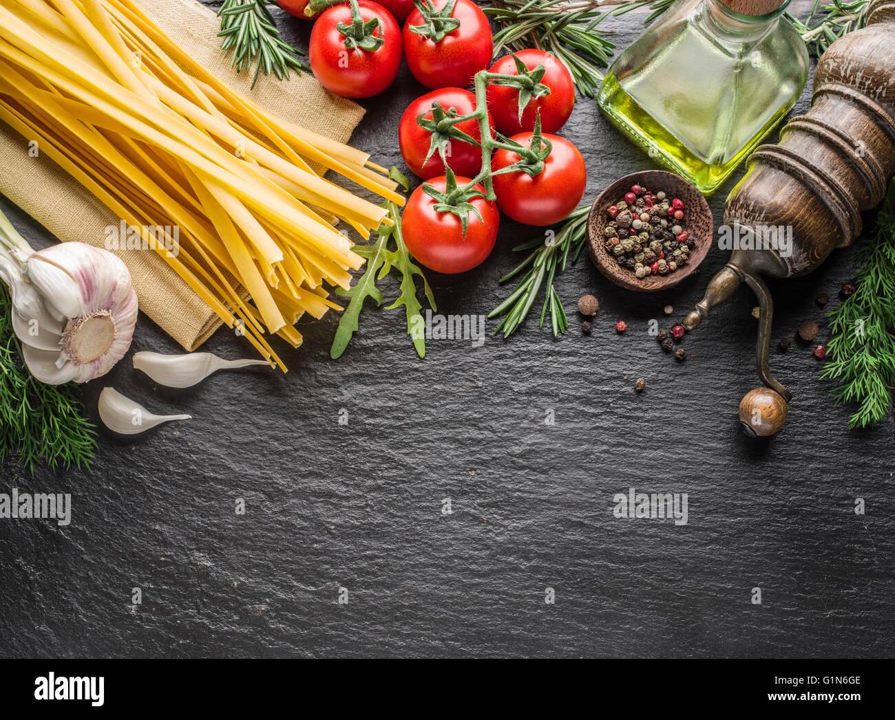 Pasta Zutaten. Cherry-Tomaten, Spaghetti Nudeln, Rosmarin und Gewürze auf einem Graphit-Brett. Stockfoto
