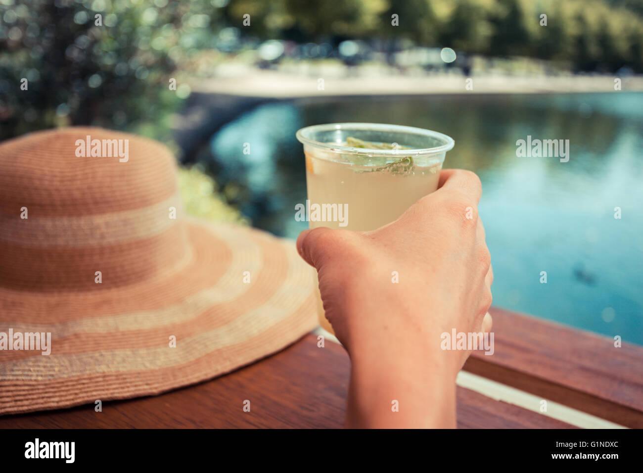 Eine junge Frau ist von einem Teich im Park Limonade trinken. Stockbild