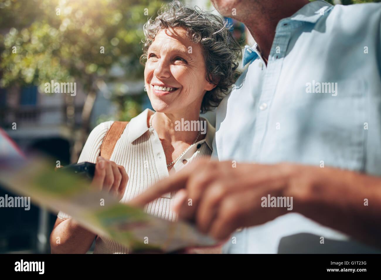Ältere Frau mit einem Mann hält einen Stadtplan. Glücklich und fröhlich, in den Ruhestand genießen. Stockbild
