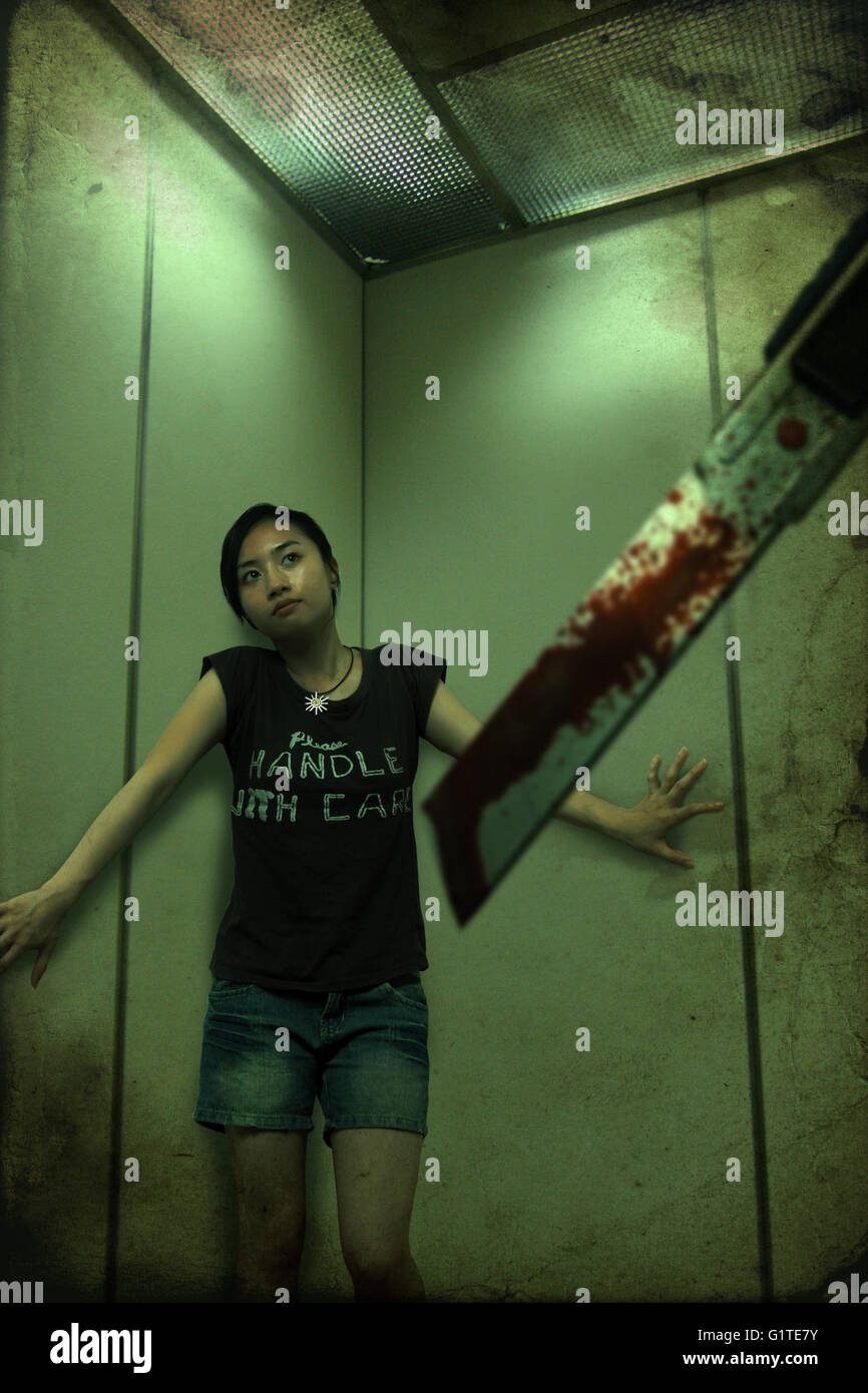 eine Mädchen in den Lift zu behandeln, aus einem Fräser chinesische Gespenstergeschichte schreckliche Stockbild