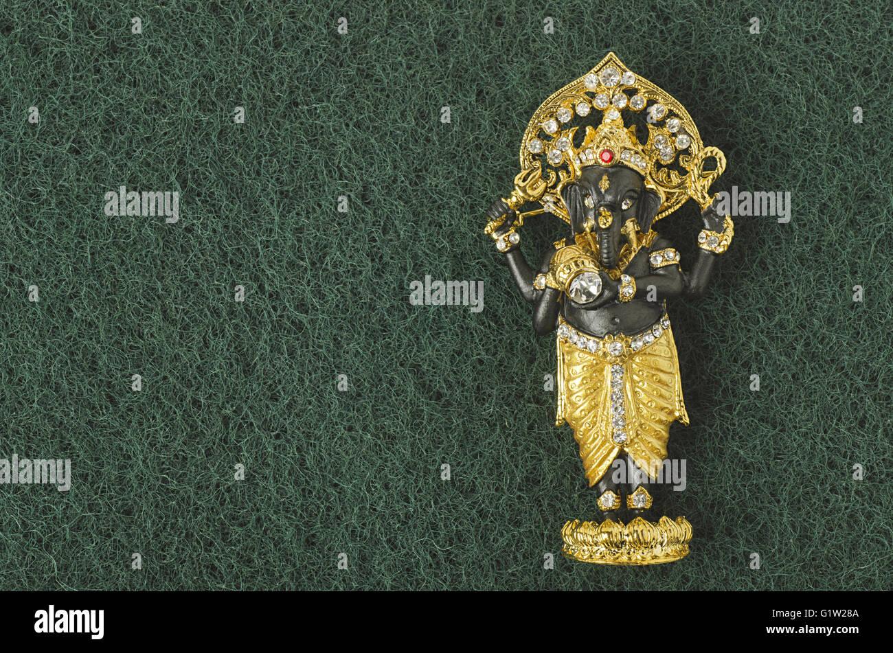 Kleines Idol (Miniatur) von Lord Ganesha mit dem Hintergrund des Grases, Studio gedreht, Pune, Maharashtra, Indien Stockbild