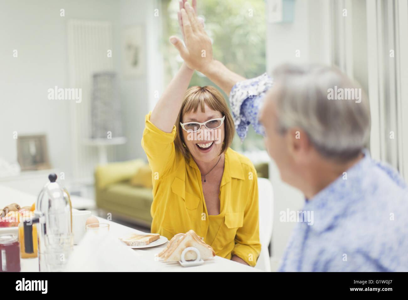 Begeisterte älteres paar fiving beim Frühstück Stockbild