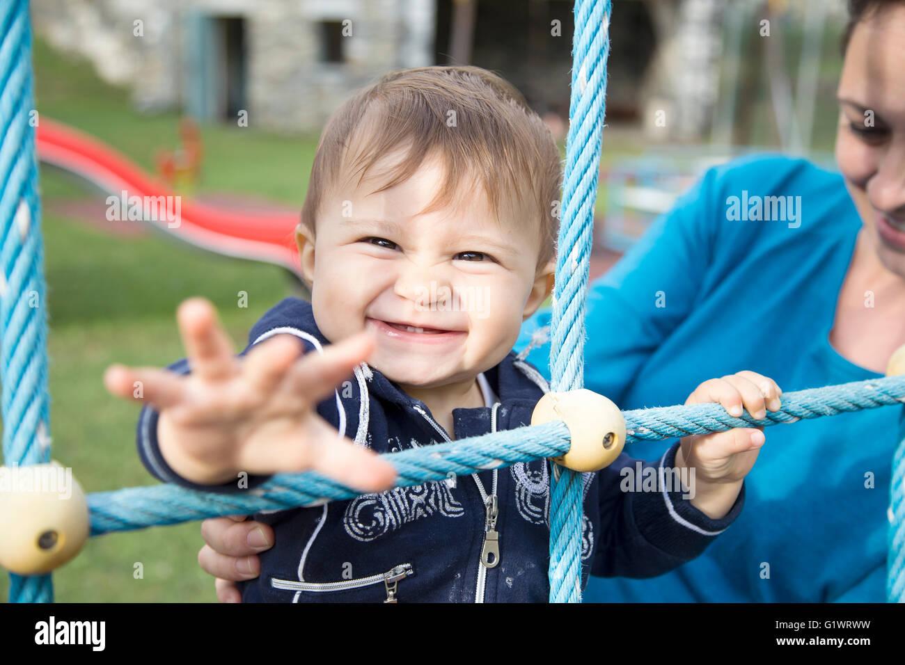 Mutter mit einjährige Tochter ziehen den Arm beim Blick in die Kamera Stockfoto