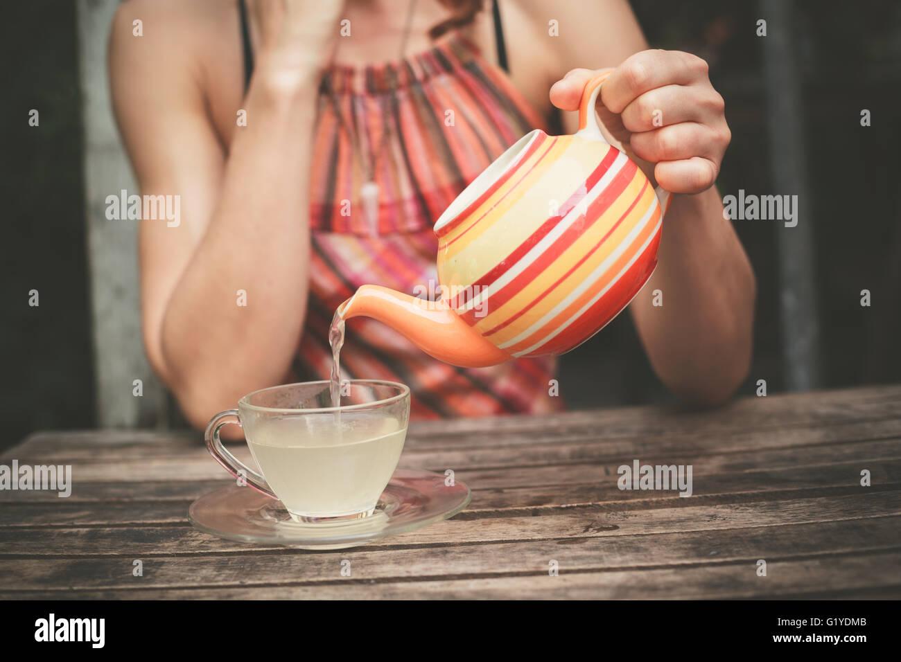 Eine junge Frau sitzt an einem Tisch und gießt sich eine Tasse Tee Stockbild