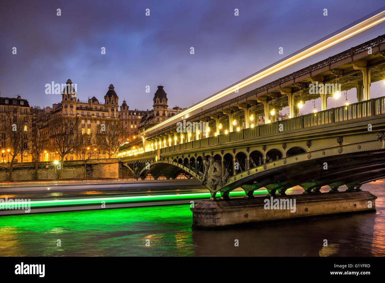 Paris-Bir-Hakeim-Brücke in der Dämmerung mit Wolken und Lichtspuren der Boote auf dem Fluss Seine. 16. Arrondissement Stockfoto