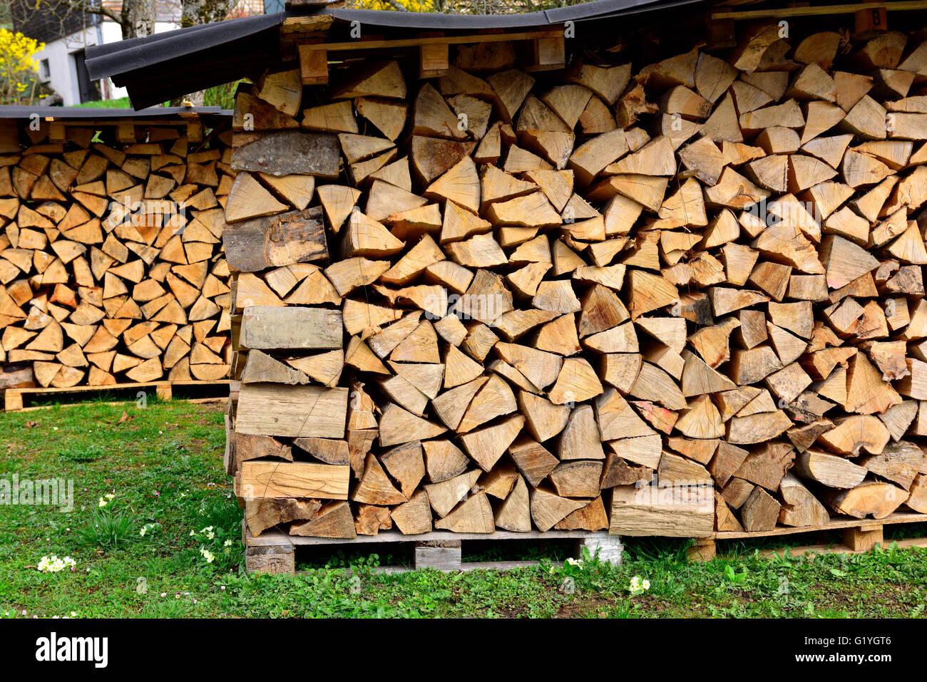 Stapel von Protokollen für Brennholz unter Blechdach würzen Stockbild