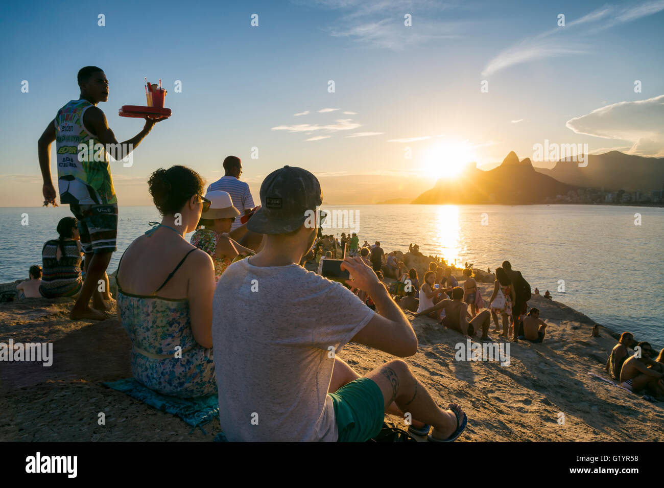 RIO DE JANEIRO - 26. Februar 2016: Massen von Menschen versammeln, um den Sonnenuntergang auf den Felsen am Arpoador Stockbild