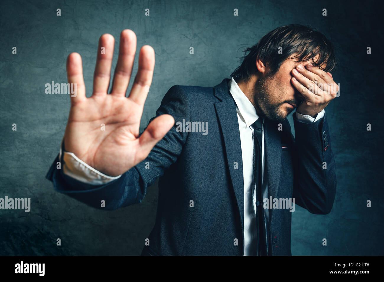 Betonte Geschäftsmann nach Projekt scheitern, Augen in Verzweiflung und Gestikulieren Stop Kamera Hand bedecken. Stockbild