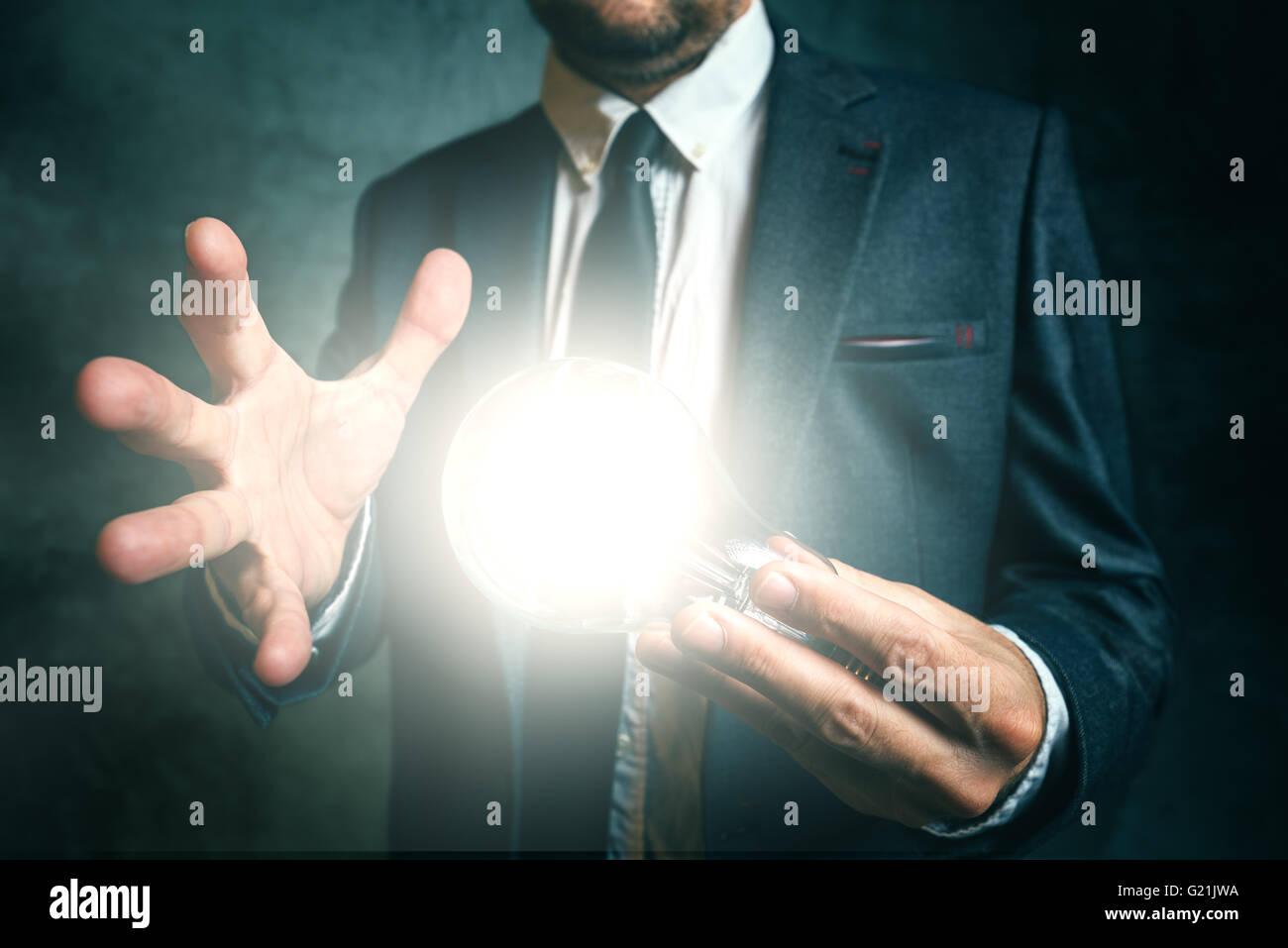 Unternehmen Kreativität und Vision-Konzept mit eleganten Erwachsenen Geschäftsmann hält helle Glühbirne als Metapher Stockfoto