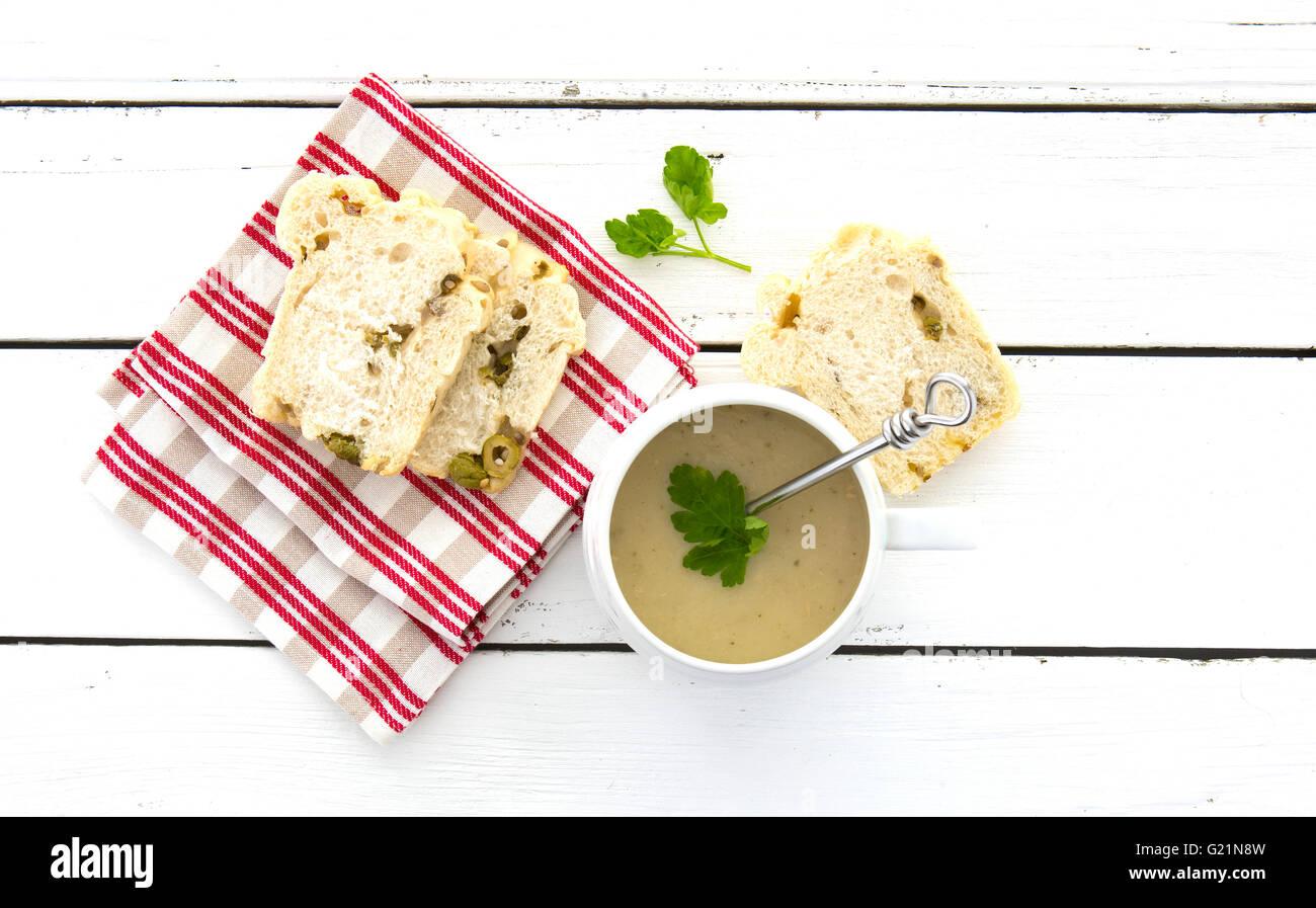 Huhn und Zitrone Suppe mit Oliven Brot auf einem weißen Holztisch Stockbild