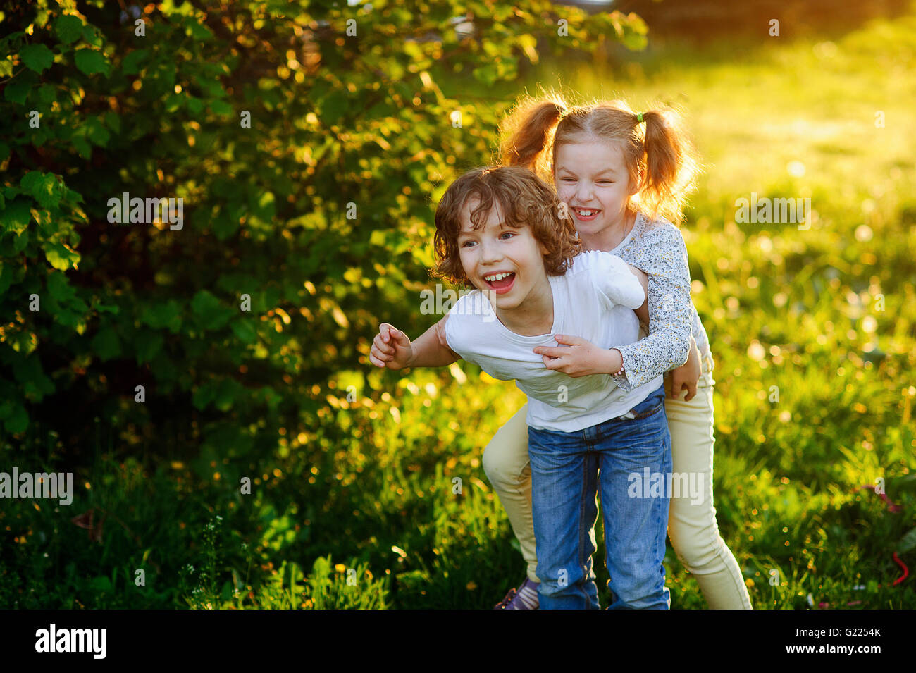Blonder Junge und Mädchen spielen park Stockbild