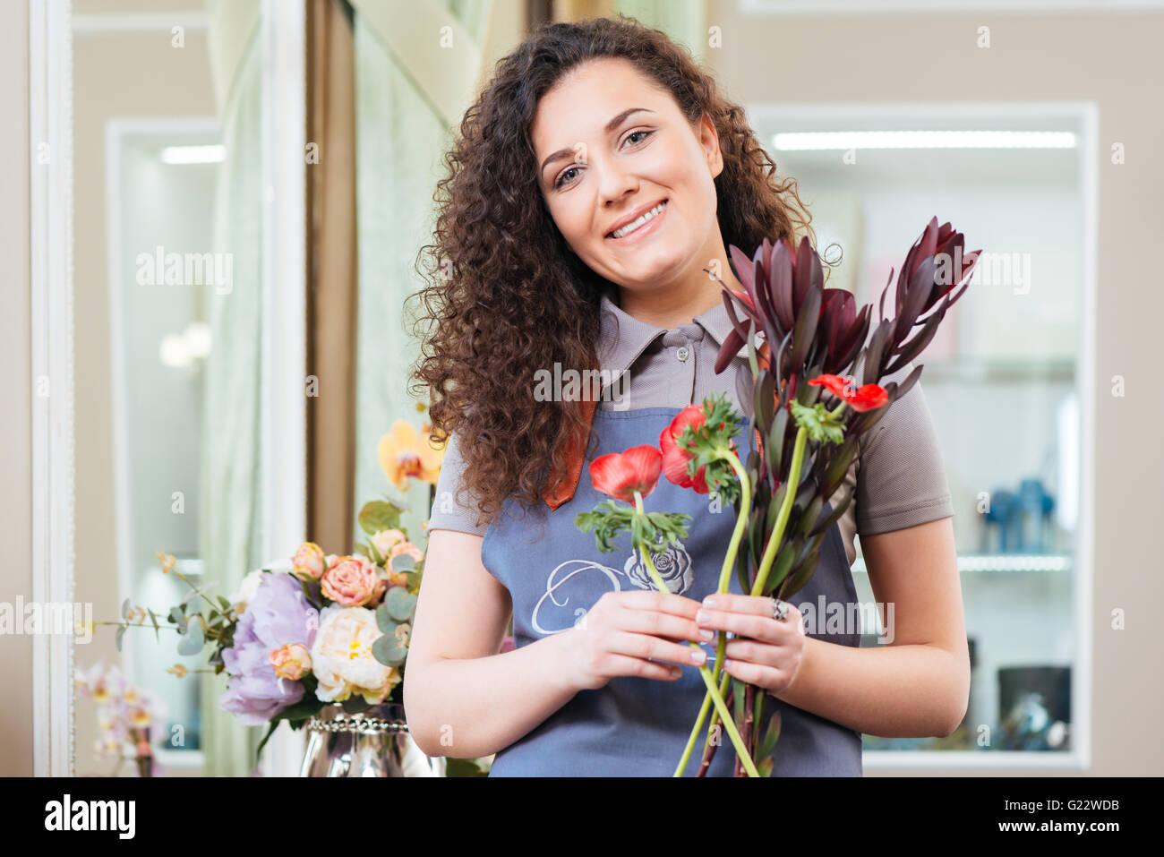 Porträt von schönen lockigen Frau Florist im Blumenladen Stockbild