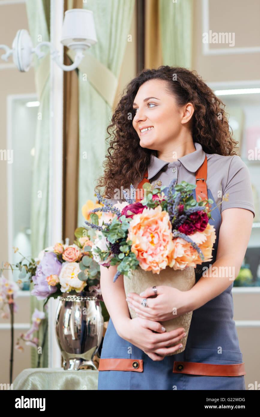 Attraktive lächelnde junge Frau Floristen stehen und halten Vase mit Blumen im shop Stockbild