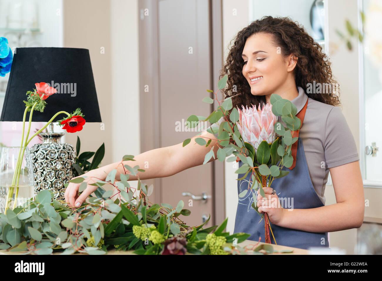 Glücklich attraktive junge Frau Floristen machen Blumenstrauß auf dem Tisch im shop Stockbild