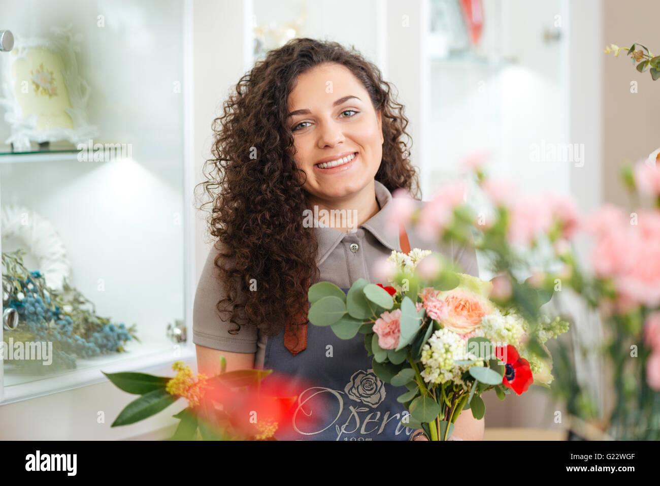 Fröhliche, schöne junge Frau Floristen bei der Arbeit im Blumenladen Stockbild
