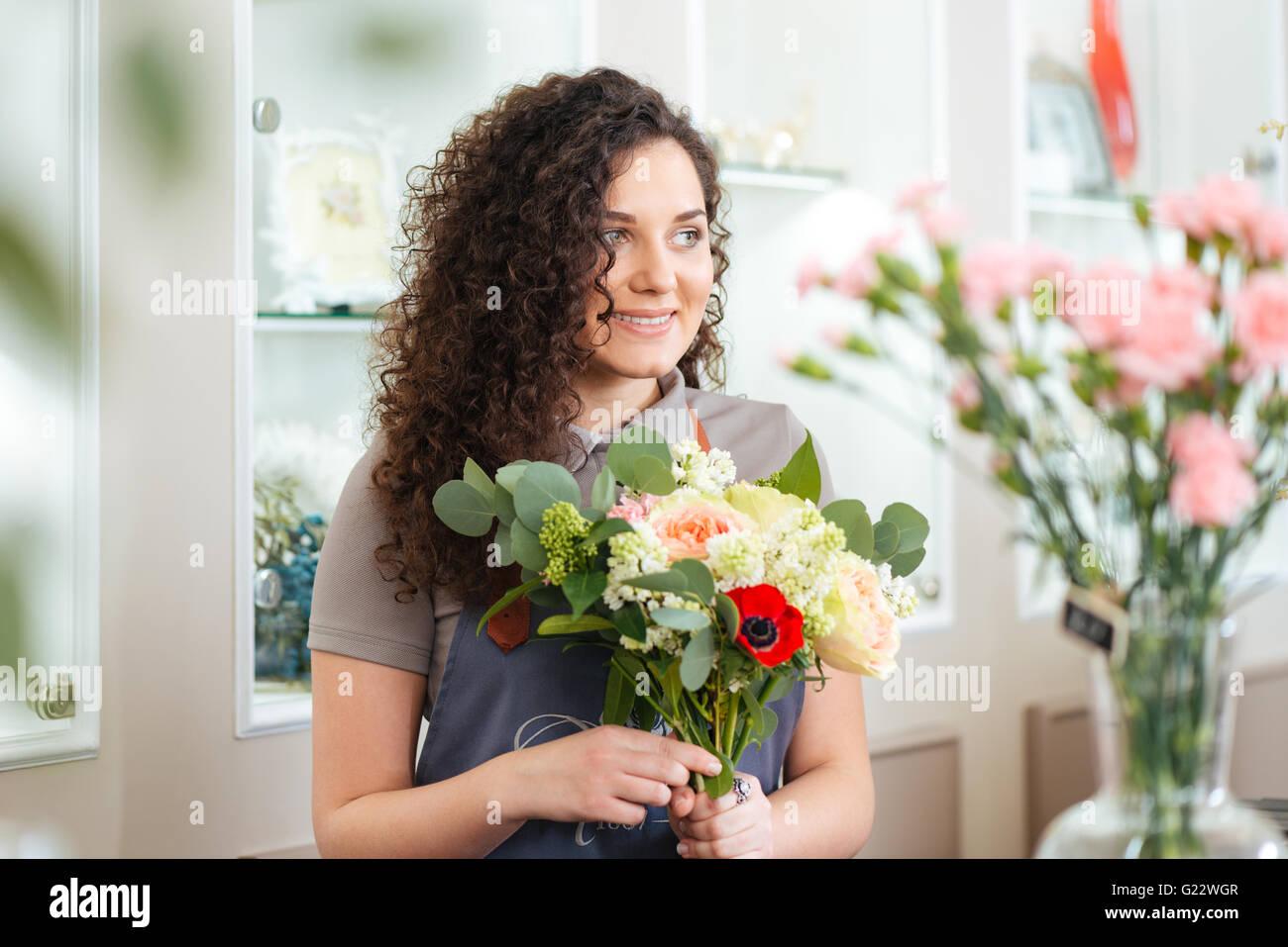 Gerne nette junge Frau Florist arbeiten im Blumenladen Stockbild