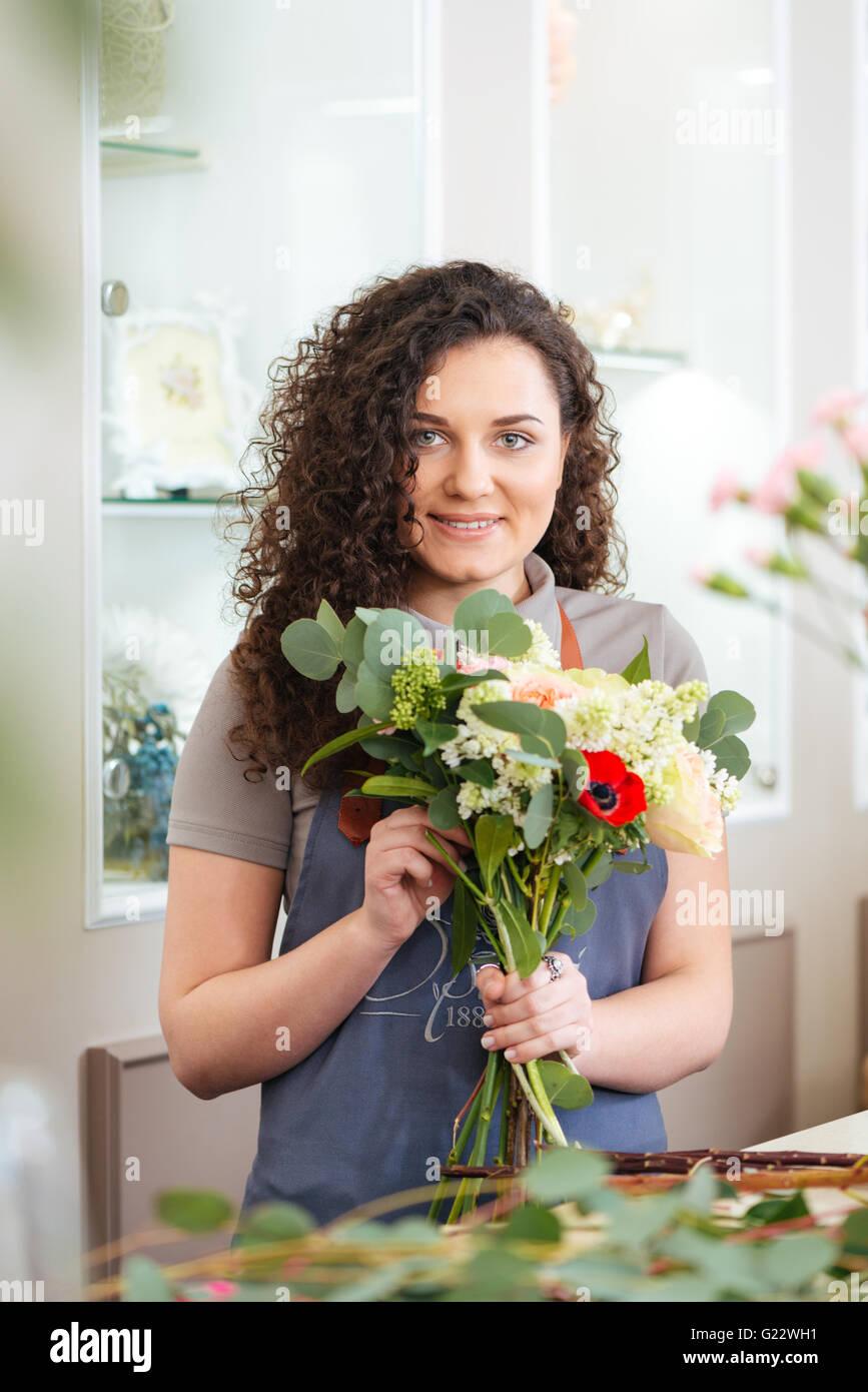 Lächelnd, hübsche junge Frau Florist genießen arbeiten im Blumenladen Stockbild