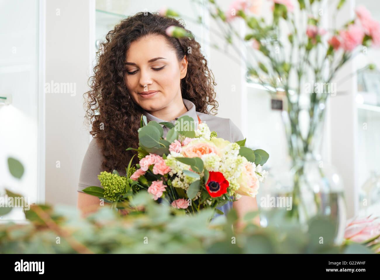 Porträt von schönen lockigen jungen Frau Floristen mit Blumenstrauß arbeitet in shop Stockbild