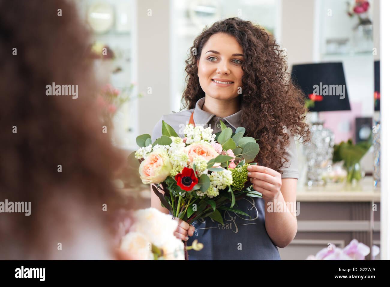 Fröhliche, schöne junge Frau Floristen halten Blumenstrauß und Blick auf den Spiegel Stockbild