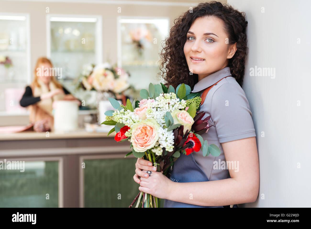 Porträt von Floristen gerne hübsche junge Frau mit Blumenstrauß im Blumenladen Stockbild